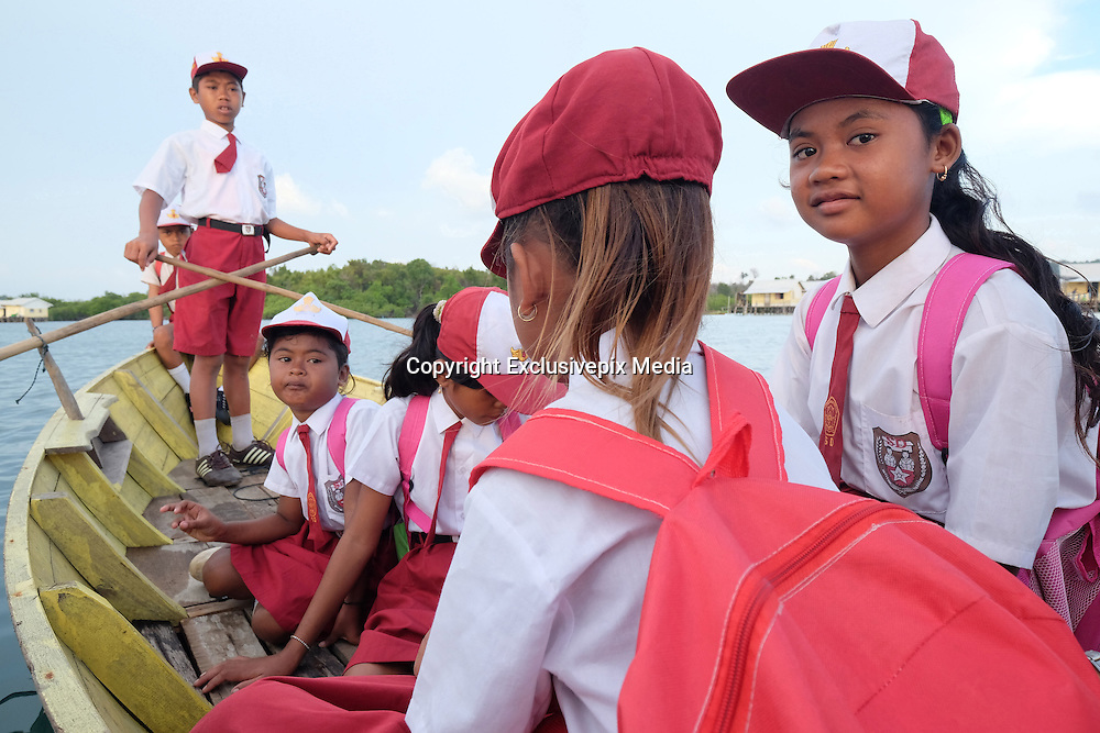 LINGGA, INDONESIA - <br /> <br /> Sea Tribe Children in Indonesia, Last Nomad Tribe Sea in Indonesia<br /> <br /> Children of sea tribal or called sea people goes to school with wooden canoe at Tajur Biru island on December 17, 2014 in Lingga, Riau Islands province, Indonesia.<br /> Sea Tribe or called sea people who inhabit Tajur Biru Island, Lingga Regency, Riau Islands Province - Indonesia, sea people is the last existing tribe. <br /> only 15 families 52 people in total. Sea people are wandering tribes who live in the sea. The indigenous people called the sea because it has characteristics specific life, such as family life in the boat and wander along the waters.<br /> Historically, Sea People used to be a pirate, but it plays an important role in the kingdom of Srivijaya, the Sultanate of Malacca and Johor Sultanate. They keep the straits, repel pirates, guiding traders to harbor , and maintain their hegemony in the region.<br /> ©Exclusivepix Media