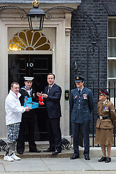 © Licensed to London News Pictures. 23/10/2014. London, UK. The British Prime Minister, David Cameron and members of the Armed Forces buy poppies from the Royal British Legion outside 10 Downing Street in central London to mark the launch of the 2014 Poppy Appeal. Photo credit : Vickie Flores/LNP