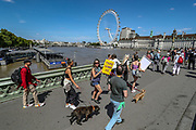 """A group of protestors who appears to be against 5G network, against the pandemic outbreak, as well as a vaccine solution, are seen protesting over the Westminster Bridge on Monday, June 22. 2020. They also said that government lockdown rules that aim to curb the spread of coronavirus outbreak quote: """"are a farse that should be challenged."""" The group appears to willingly challenge the two-metre social distancing rule, which will be under review as the UK relax coronavirus lockdown measures implemented to stem the spread of the virus. (Photo/ Vudi Xhymshiti)"""