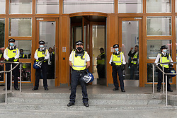 © Licensed to London News Pictures. 03/09/2021. London, UK. Police officers guard the entrance to a Cabot Square building during an anti-lockdown and anti-vaccination demonstration in Canary Wharf calling for an end to mandatory vaccination passports and vaccination of teenagers. Photo credit: London News Pictures