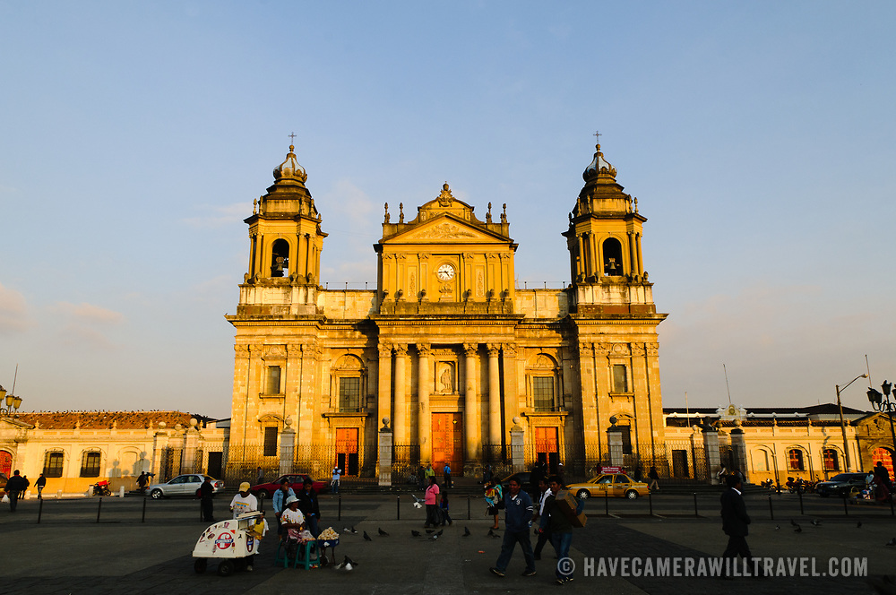 Catedral Metropolitana is lit up by the golden light of the setting sun facing Parque Central (officially the Plaza de la Constitucion) in the center of Guatemala City, Guatemala.