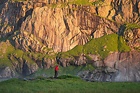 Photographer in front of large cliff, Lofoten Islands, Norway
