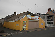 Boarded up Amusements arcade building in the seaside town of Borth on a grey gloomy day in Wales, United Kingdom.