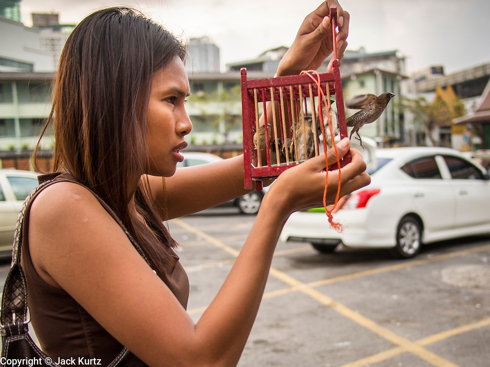 """14 FEBRUARY 2014 - BANGKOK, THAILAND:  A woman releases a bird to make merit on Makha Bucha Day at Wat That Thong (also called Wat Tad Tong) in Bangkok. The aims of Makha Bucha Day are: not to commit any kind of sins, do only good and purify one's mind. It is a public holiday in Cambodia, Laos, Myanmar and Thailand. Many people go to the temple to perform merit-making activities on Makha Bucha Day. The day marks four important events in Buddhism, which happened nine months after the Enlightenment of the Buddha in northern India; 1,250 disciples came to see the Buddha that evening without being summoned, all of them were Arhantas, Enlightened Ones, and all were ordained by the Buddha himself. The Buddha gave those Arhantas the principles of Buddhism, called """"The ovadhapatimokha"""". Those principles are:  1) To cease from all evil, 2) To do what is good, 3) To cleanse one's mind. The Buddha delivered an important sermon on that day which laid down the principles of the Buddhist teachings. In Thailand, this teaching has been dubbed the """"Heart of Buddhism.""""   PHOTO BY JACK KURTZ"""
