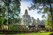 "02 JULY 2013 - ANGKOR WAT, SIEM REAP, SIEM REAP, CAMBODIA:  The Bayon in the complex at Angkor. Angkor Wat is the largest temple complex in the world. The temple was built by the Khmer King Suryavarman II in the early 12th century in Yasodharapura (present-day Angkor), the capital of the Khmer Empire, as his state temple and eventual mausoleum. Angkor Wat was dedicated to Vishnu. It is the best-preserved temple at the site, and has remained a religious centre since its foundation – first Hindu, then Buddhist. The temple is at the top of the high classical style of Khmer architecture. It is a symbol of Cambodia, appearing on the national flag, and it is the country's prime attraction for visitors. The temple is admired for the architecture, the extensive bas-reliefs, and for the numerous devatas adorning its walls. The modern name, Angkor Wat, means ""Temple City"" or ""City of Temples"" in Khmer; Angkor, meaning ""city"" or ""capital city"", is a vernacular form of the word nokor, which comes from the Sanskrit word nagara. Wat is the Khmer word for ""temple grounds"", derived from the Pali word ""vatta."" Prior to this time the temple was known as Preah Pisnulok, after the posthumous title of its founder. It is also the name of complex of temples, which includes Bayon and Preah Khan, in the vicinity. It is by far the most visited tourist attraction in Cambodia. More than half of all tourists to Cambodia visit Angkor.         PHOTO BY JACK KURTZ"