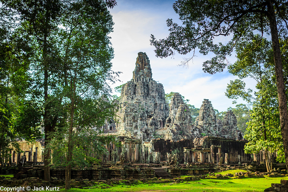 """02 JULY 2013 - ANGKOR WAT, SIEM REAP, SIEM REAP, CAMBODIA:  The Bayon in the complex at Angkor. Angkor Wat is the largest temple complex in the world. The temple was built by the Khmer King Suryavarman II in the early 12th century in Yasodharapura (present-day Angkor), the capital of the Khmer Empire, as his state temple and eventual mausoleum. Angkor Wat was dedicated to Vishnu. It is the best-preserved temple at the site, and has remained a religious centre since its foundation– first Hindu, then Buddhist. The temple is at the top of the high classical style of Khmer architecture. It is a symbol of Cambodia, appearing on the national flag, and it is the country's prime attraction for visitors. The temple is admired for the architecture, the extensive bas-reliefs, and for the numerous devatas adorning its walls. The modern name, Angkor Wat, means """"Temple City"""" or """"City of Temples"""" in Khmer; Angkor, meaning """"city"""" or """"capital city"""", is a vernacular form of the word nokor, which comes from the Sanskrit word nagara. Wat is the Khmer word for """"temple grounds"""", derived from the Pali word """"vatta."""" Prior to this time the temple was known as Preah Pisnulok, after the posthumous title of its founder. It is also the name of complex of temples, which includes Bayon and Preah Khan, in the vicinity. It is by far the most visited tourist attraction in Cambodia. More than half of all tourists to Cambodia visit Angkor.         PHOTO BY JACK KURTZ"""