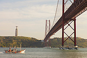 A fishing boat going out of Lisbon's harbour, with Cristo-Rei (King Christ) monument and 25th of April bridge in the background.