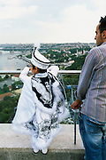 From a lookout point next to Pierre Lofti Cafe in Istanbul, Turkey, a boy who will soon be circumcised looks out over the Golden Horn. As custom dictates, the boy is dressed up as a small sultan or prince. A relative stands beside him, holding his sceptre. During the days leading up to the circumcision, it is customary that boys about to be circumcised  are taken on a tour of some of the famous mosques and landmarks of the city.
