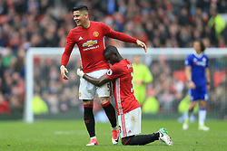 16th April 2017 - Premier League - Manchester United v Chelsea - Eric Bailly of Man Utd kneels on the ground as he hugs teammate Marcos Rojo after their victory - Photo: Simon Stacpoole / Offside.