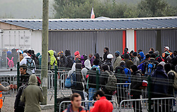 © Licensed to London News Pictures. 24/10/2016. Calais, France. Migrants queue to be processed inside the 'jungle' camp, as the evacuation and demolition begins at the migrant camp in Calais, known as the 'Jungle'. French authorities have given an eviction order to thousands of refugees and migrants living at the makeshift living area of the French coast. Photo credit: Ben Cawthra/LNP