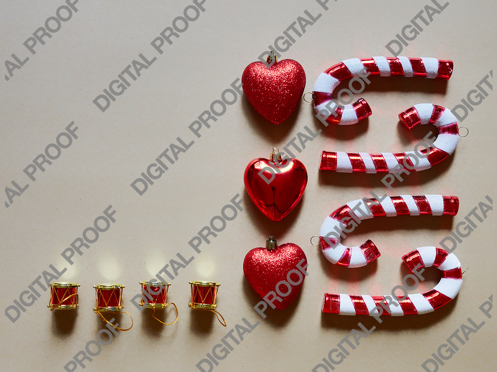 Christmas candy cane drums hearts and gifts at studio above view over a brown cream neutral background isolated flatlay