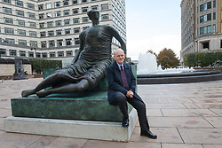 © Licensed to London News Pictures. 25/10/2017. LONDON, UK.  John Biggs, Mayor of Tower Hamlets looks at Henry Moore's sculpture, Draped Seated Woman 1957, affectionately known as 'Old Flo' after it is installed in Cabot Square, Canary Wharf, east London after 20 years on public display at the Yorkshire Sculpture park. The iconic sculpture was loaned to Yorkshire by the London Borough of Tower Hamlets in 1997, after the Stifford Estate in Stepney where it had been located since 1962 was demolished. The return of the sculpture to London marks an end to a bitter political battle over Old Flo. In 2012 the disgraced former mayor of Tower Hamlets Lutfur Rahman, declared that it should be sold to raise £20m, that sparked protests & a court battle over who actually owned the sculpture. Tower Hamlets was confirmed as the legal owner in 2015.  Photo credit: Vickie Flores/LNP