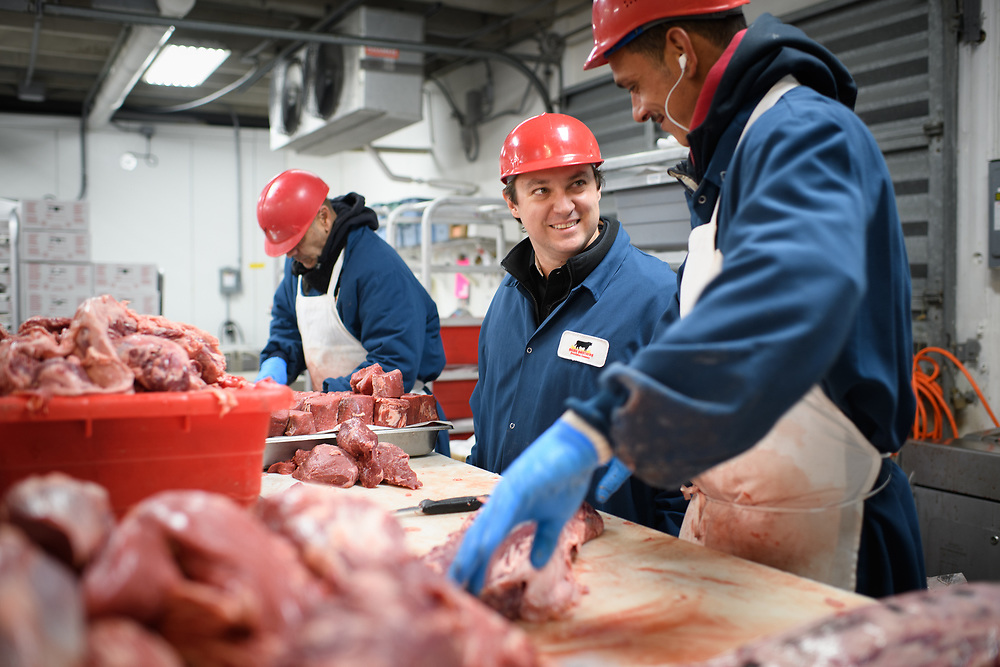 Supervisor inspecting workers at a beef processing facility.
