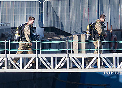 © Licensed to London News Pictures. 12/02/2018. London, UK. Members of a Royal Navy Bomb Disposal Team arrive to look at the scene near London City Airport which remains closed after a World War II era bomb was found in The River Thames during routine work on nearby King V Dock. Police have evacuated nearby residents, closed the airport and set up a 214-metre exclusion zone. Photo credit: Peter Macdiarmid/LNP