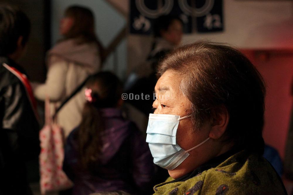 elderly Japanese woman wearing a breathing mask