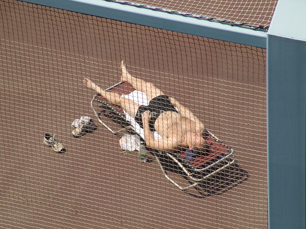 man sunbathing on rooftop