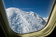 Mount Rainier, the tallest volcano in the Cascade Range, is framed by a passenger window of a Boeing 737 in this aerial view over Washington state.