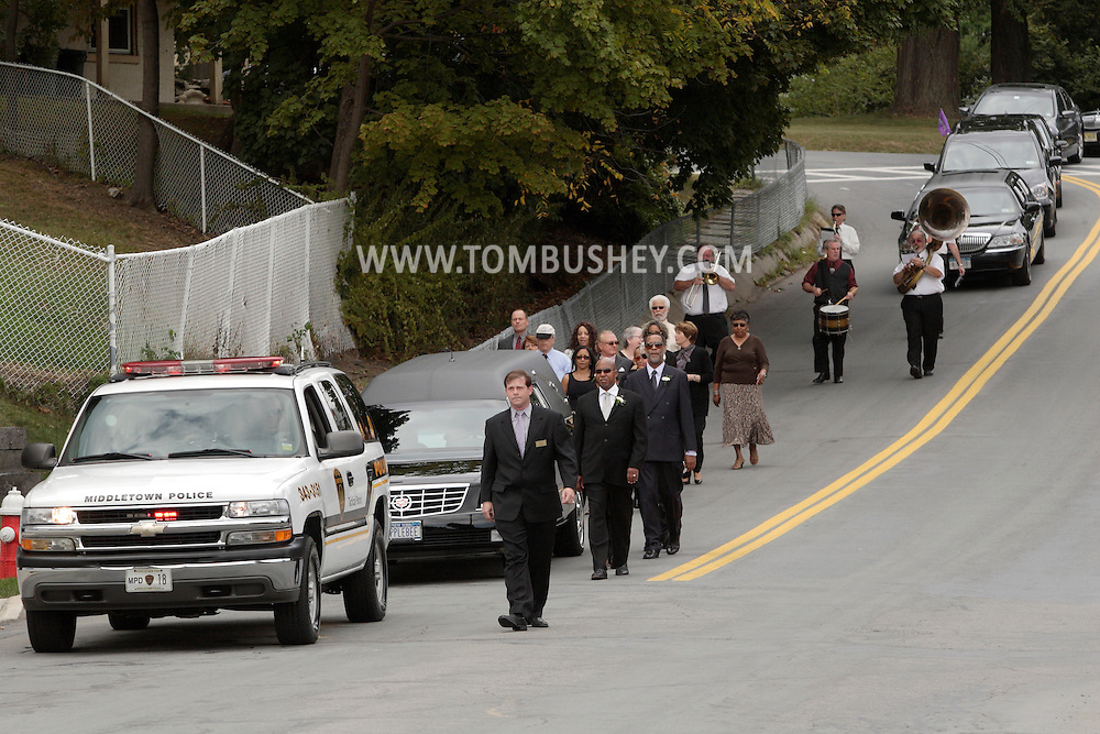 Middletown, New York -  Mourners walk alongside the hearse and are followed by a Dixieland band in the funeral procession  for Willie Carter on West Main Street on Sept. 8, 2010.
