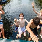 NLD/Amsterdam/20150702 - kinderen springen van de brug in het kanaal op wat verkoeling te zoeken tijdens de warmte