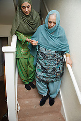 South Asian woman helping her mother on stairs.