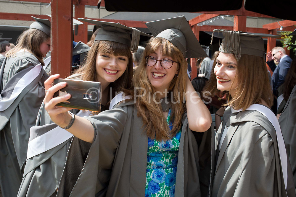 Young graduates wearing rented gowns and mortarboards smile for their selfie photo at a private party before their university graduation ceremony, on 13th July 2017, at the University of York, England.