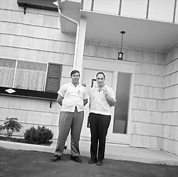 two men standing in front of a suburban home in the 1960's