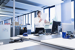 Businesswoman standing and reading document in office, Freiburg Im Breisgau, Baden-Württemberg, Germany