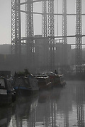 House boats moored on the Regent's Canal on a misty morning on 27th of November 2020 in Hackney, London, United Kingdom. The canal near Broadway Market is a popular place for house boats to moor. In the back ground are the now abandoned gas works, with it's structures disappearing into the mist.