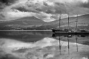 Old fishing trawler at harbour on the shores of Loch Fyne at Inverary with calm waters and dramatic skies.