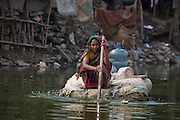 A woman paddles a raft made of discarded lightweight refuse in the Banani Lake slum district. She gathers water in plastic jugs and bottles from a public spigot on the other side of the lake to bring back to her slum home on an island in the lake.