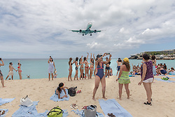 Tourist Line Up To Get Photo With Jet Passing Over Beach