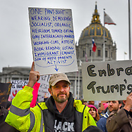 """In Civic Center Plaza a man holds a sign with above his head and an arrow pointing to himself. The sign reads, """"One pant-suit-wearing, democratic, socialist, organic heirloom tomato-eating, gay-interracially-married working class, atheist, book-reading, voting, immigrant, feminist son of hippie-parents activist."""""""