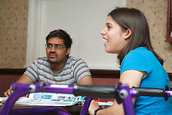 Young white student, who has Cerebral Palsy and uses a walking frame, in study group with asian student.