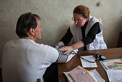 Dr Lydia Drishko takes the blood pressure reading for a patient during a consultation at an MSF mobile clinic in the village of Sukodolsk near to Lugansk.