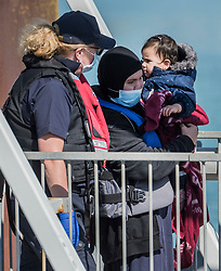 © Licensed to London News Pictures. 08/09/2021. Dover, UK. A Border Force officer helps a mother and young migrant ashore as they arrive at Dover Harbour in Kent after crossing the English Channel. Fine weather is expected to see migrants attempt to cross the English Channel to the UK this week.  Photo credit: Stuart Brock/LNP