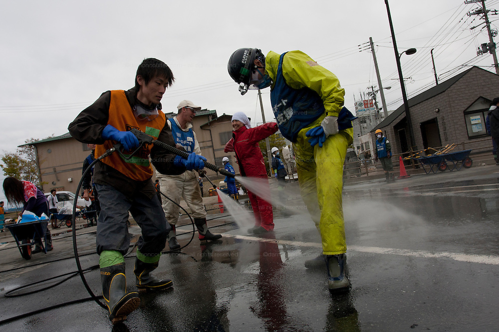 Peace boat volunteers wash themselves free of mud and dust after taking part in the clean-up operations in Ishinomaki, Miyagi Friday May 6th 2011. Around 350 volunteers took part in the relief effort over the Golden Week holiday, including 41 foreigners, clearing mud and removing debris from this coastal town which more almost levelled in the March 11th earthquake and tsunami.