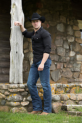 cowboy standing by a rustic ranch cabin