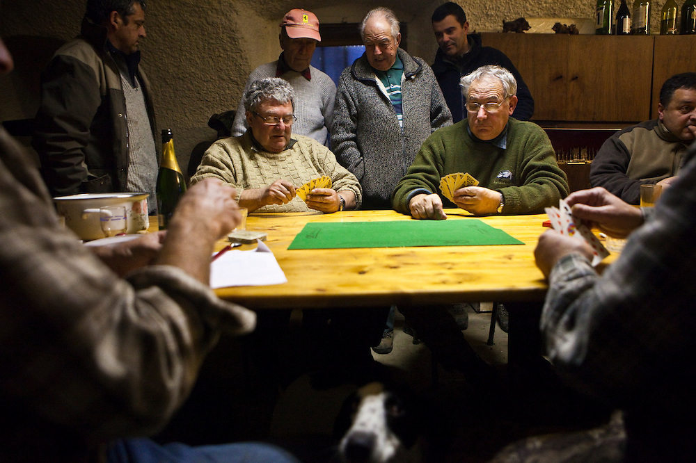 Members of the village's hunting association play cards at their headquarters after a successful hunt in Barnave, Drôme valley, France. A pet dog looks on from under the table.