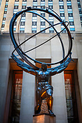 """Atlas is a bronze statue in front of Rockefeller Center in midtown Manhattan, New York City, across Fifth Avenue from St. Patrick's Cathedral. The sculpture depicts the Ancient Greek Titan Atlas holding the heavens. It was created by sculptor Lee Lawrie with the help of Rene Paul Chambellan, and it was installed in 1937.<br /> <br /> The sculpture is in the Art Deco style, as is the entire Rockefeller Center. Atlas in the sculpture is 15 feet tall, while the entire statue is 45 feet tall, as high as a four-story building. It weighs 7 tonnes and is the largest sculpture at Rockefeller Center. The North-South axis of the armillary sphere on his shoulders points towards the North Star as seen from New York City.<br /> <br /> When Atlas was unveiled in 1937, some people protested, claiming that it looked like Italian dictator Benito Mussolini. Later, painter James Montgomery Flagg said that Atlas """"looks too much as Mussolini thinks he looks""""."""