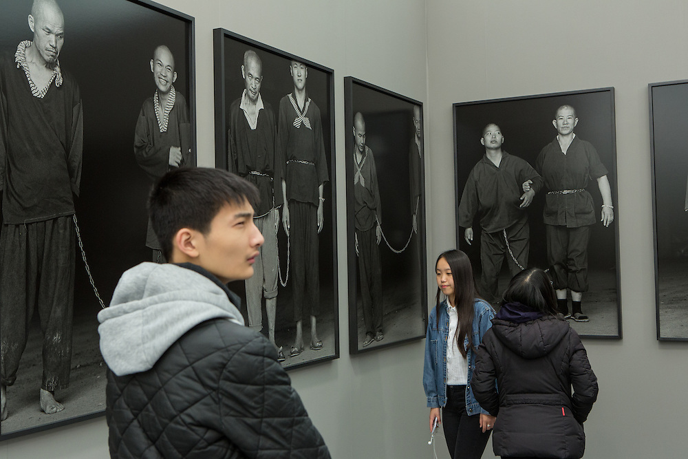 """New York, NY - 6 May 2016. Frieze New York art fair. Visitors among the large-scale silver-gelatin photos by Magnum photographer Chien-Chi Chang, from his series """"The Chain"""", in the Chi-Wen Gallery of Taipei."""
