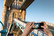 Tourist taking photos with smart phones at Tower Bridge, London, England, UK