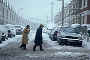 Making their way across a snow-swept road in Norwood, south London, an elderly couple tread warily as the snow turns to slush. It's a bleak, raw morning as the new snowfall has settled on this suburban street where cars are parked on icy kerbs. Wearing sensible hats and coats and non-slip boots the pensioners are vulnerable to icy black spots which may endanger their stability because old people are susceptible to falls and injury at these hazardous times. A very monochrome landscape, we see little colour. Instead it is a scene of jeopardy and of an uncaring society for its older generations.