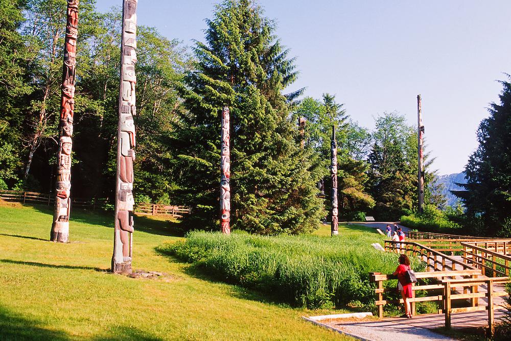 Alaska. Ketchikan. Totem Bight State Historic park. Visitors looking at Totems.