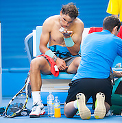 Rafael Nadal blows on his fingers after a trainer has wrapped them in a medical timeout. Nadal (ESP) turned back a strong challenge by K. Nishikori (JPN) in the men's singles division in day eight of the Australian Open. Nadal struggled at times and required a medical time out to tape his hands but he ended the day winning 7-6 (3), 7-5, 7-6 (3). The match was held at Melbourne's Rod Laver Arena.