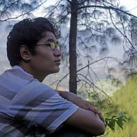 Asia, Nepal, Kathmandu. A young teenager contemplates life in nature.