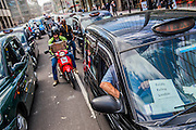 London taxi drivers block the street with a go-slow protest outside the Transport for London offices in Victoria .  They are joined by people doing the 'knowledge' on their trade mark scooters with attached clipboards. They are supported by the UGC (United cabbies Group) and are angry about the lack of a level playing field, in terms of regulation and safety standards, between black cabs and mini cabs, in particular Uber drivers.