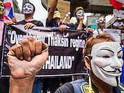 """02 JUNE 2013 - BANGKOK, THAILAND: A legless man clenches his fist while he leads a protest march through the Bangkok skywalk system. About 300 people wearing the Guy Fawkes mask popularized by the movie """"V for Vendetta"""" and Anonymous, the hackers' group, marched through central Bangkok Sunday demanding the resignation of Prime Minister Yingluck Shinawatra. They claim that Yingluck is acting as a puppet for her brother, former Prime Minister Thaksin Shinawatra, who was deposed by a military coup in 2006 and now lives in exile in Dubai.      PHOTO BY JACK KURTZ"""