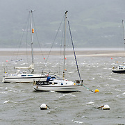 Boats moored in the bay at the mouth of the River Mawdach next to The Quay in Barmouth (Abermaw), Wales, seeking shelter from the strong winds coming in from the ocean as a major rain and wind front moves in through Wales.
