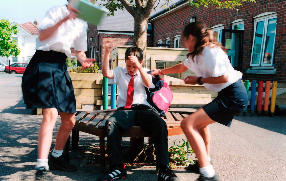 Bullying at school - girls picking on boy snatching his bag; UK. POSED BY MODELS