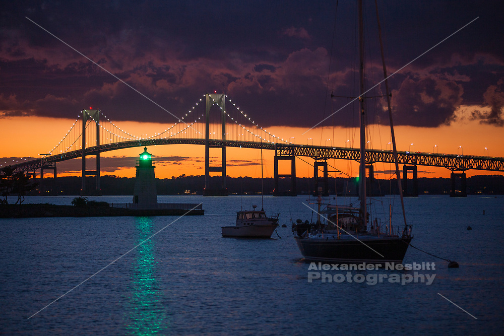 "The Green light on Goat island shines through a dramatic dark sunset from ""The point"" section of Newport, RI looking at the Newport Pell Bridge"
